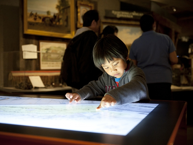 A young boy looks down and touches a large tabletop screen