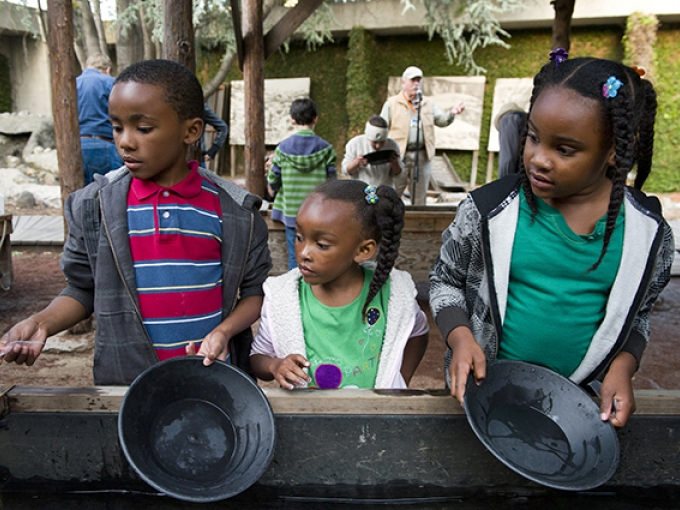 Three young children gold panning