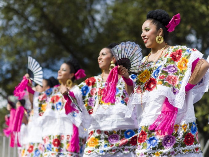 A dance group dressed in colorful matching dresses performs