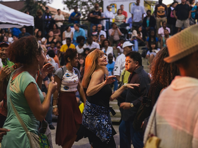 A large crowd of people at sunset dancing and smiling