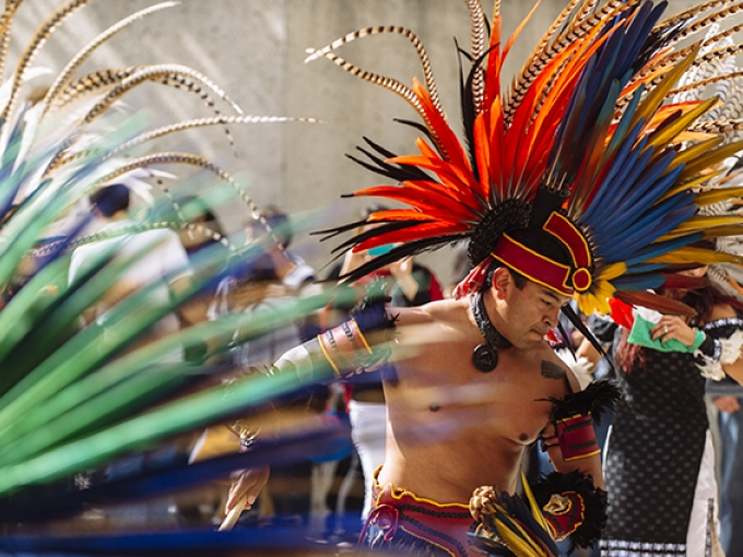 A man in a large feather headdress dancing