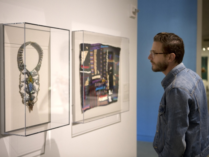A man looking at two art pieces in clear cases on the wall, on the left a large silver necklace, and on the right a colorful tapestry