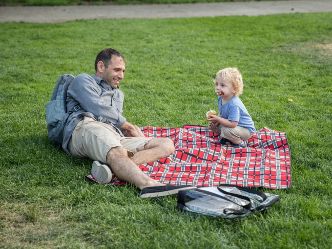 Father and son reading with Books & Blankets program in the OMCA Gardens