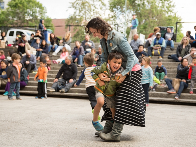 A mother and son laugh and dance together in the OMCA amphitheater