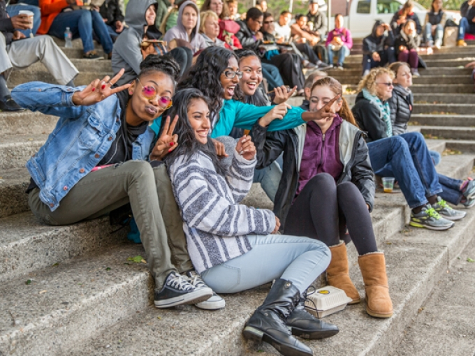 A group of teenagers pose as they sit on the amphitheater steps