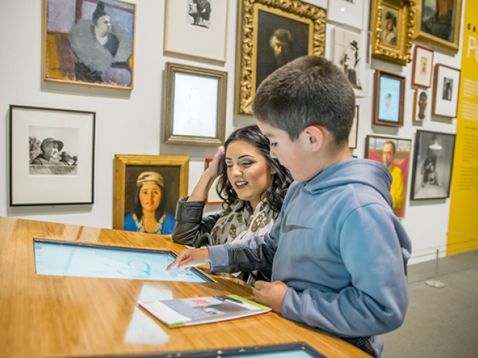A mother and son smile as they interact with a touch screen on a counter in the art gallery
