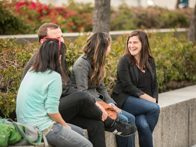Four people laugh and chat while seated on a ledge in the OMCA Gardens