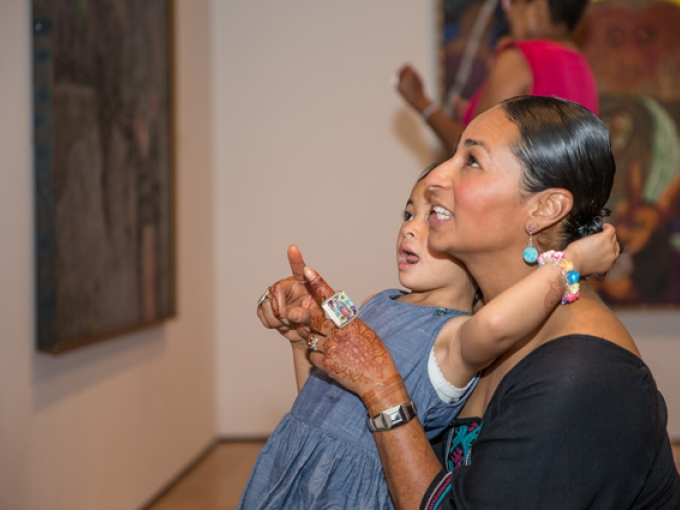 A mother and daughter look at art together