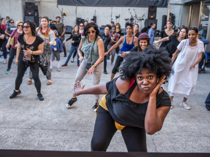 A woman poses for the camera with a large group of people behind her following dance steps