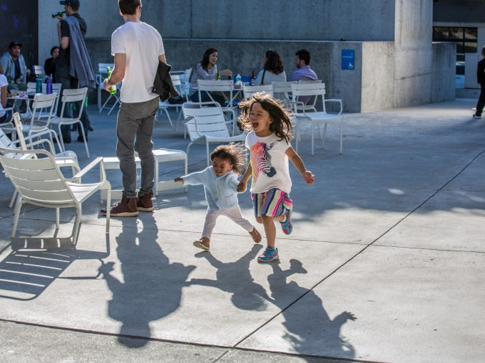 Two little girls smile and run in OMCA's Oak Street Plaza