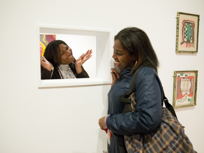Two women smile and chat with each other through a small window in a wall of OMCA's Gallery of California Art