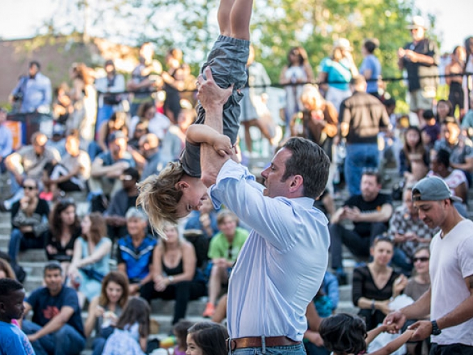A man plays with his young son, holding him upside down
