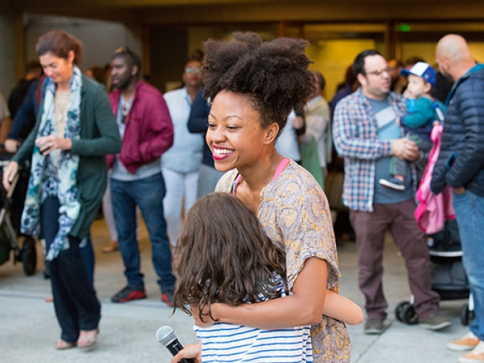 A woman gives a young girl a hug with a large crowd in the back