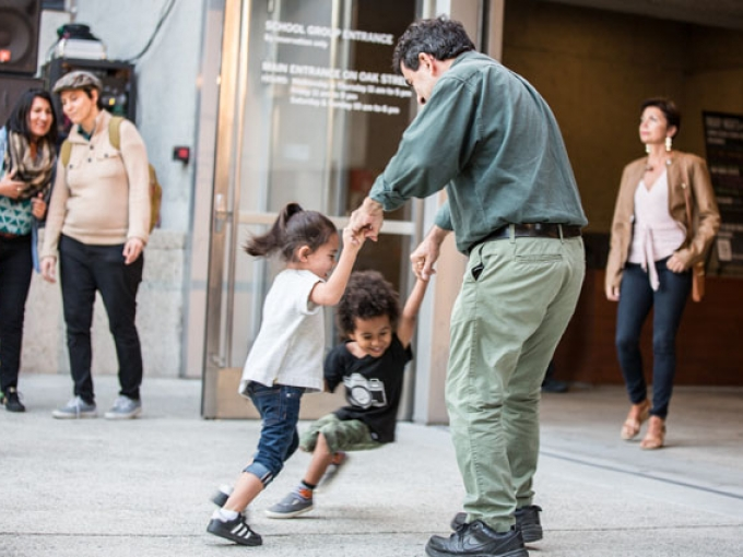 A man dancing with two children at Friday Nights at OMCA in Oakland