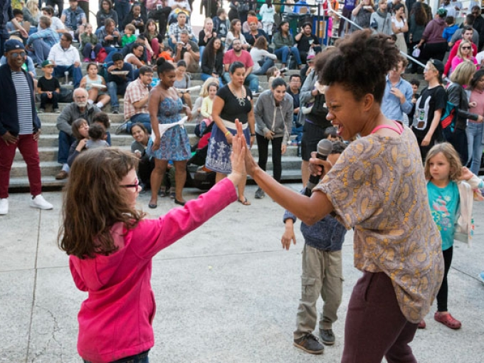 Photo of a child high-fiving a dance instructor at Friday Nights at OMCA in Oakland