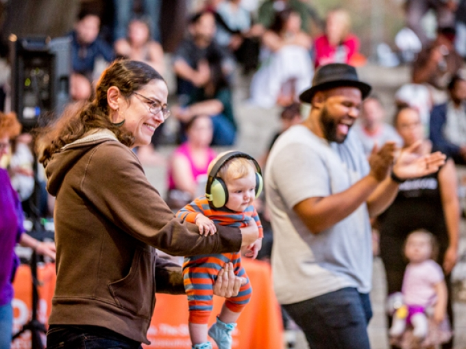 A woman holds up a baby with large headphones while a man claps in the background