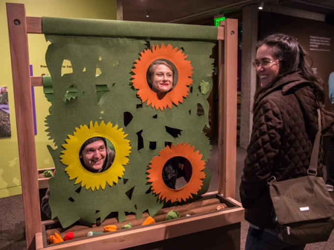 Two people put their faces in flower cut outs as a third person looks on and laughs inside the Take Root exhibition