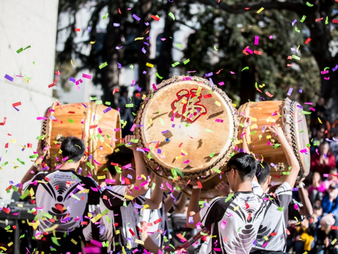 Boys holding large wooden drums with Chinese characters on them as ticker-tape confetti falls around them