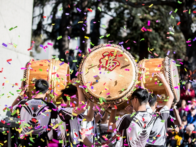 A group of young men carry several large wooden drums while colorful confetti falls around them