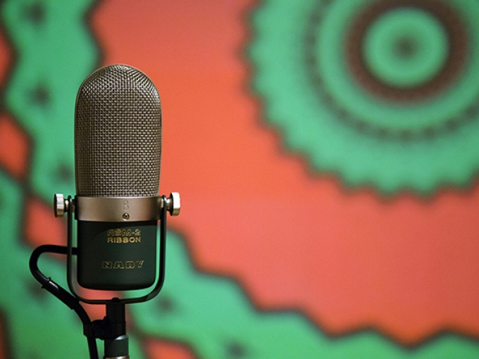 A microphone in the foreground with a green and red pattern on a screen behind ti