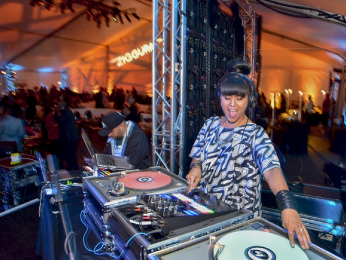 A DJ spinning a record while a crowd dances behind her