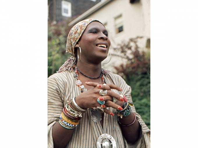 A person with a multitude of jewelry wearing their hair in two looped braids with a fuzzy headscarf