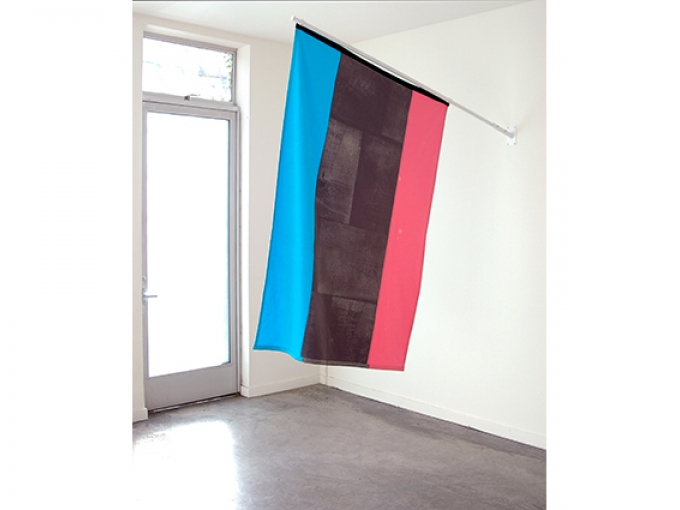 A blue, black and pink flag hangs in a bright white room