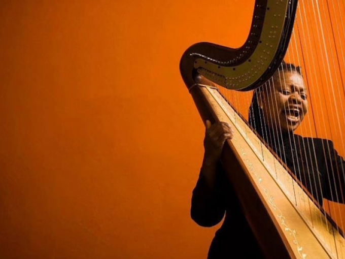 Harpist Destiny Muhammad with harp in front of an orange wall.