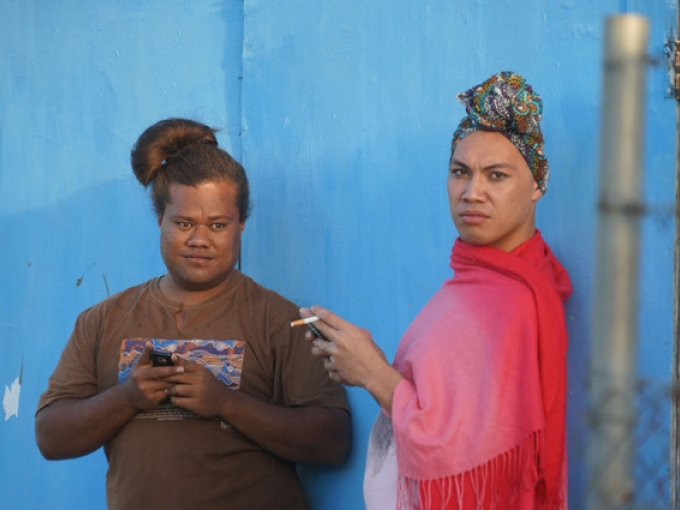 Two people stand against a bright blue wall, the rightmost person scowling at the camera