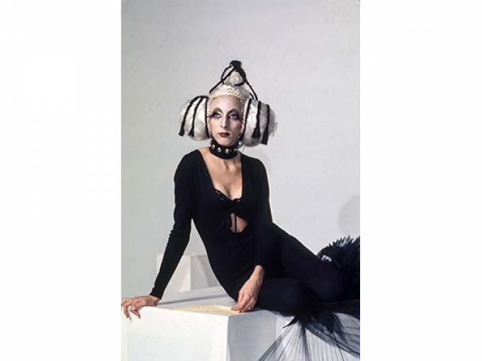 A person in a black dress with a silver headdress sits on a white box and poses