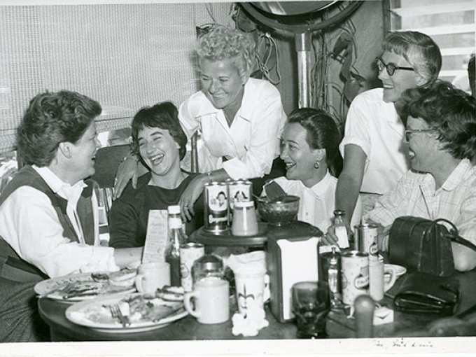 A black and white image of a group of women laughing in a booth in a diner