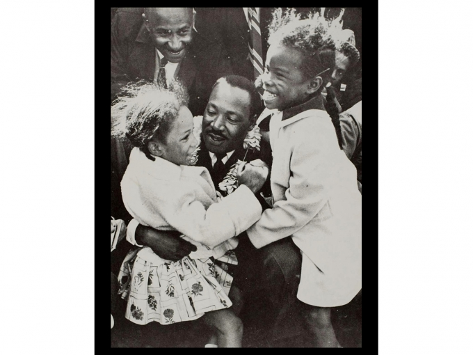 Black and white photo of Martin Luther King Jr. hugging two young girls
