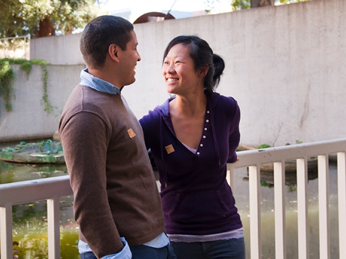 Two people smile at each other near OMCA's koi pond