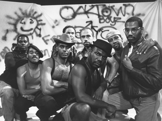 A black and white image of a group of 8 Black men in various poses in front of a spray painted sheet that says: Oaktown Boyz