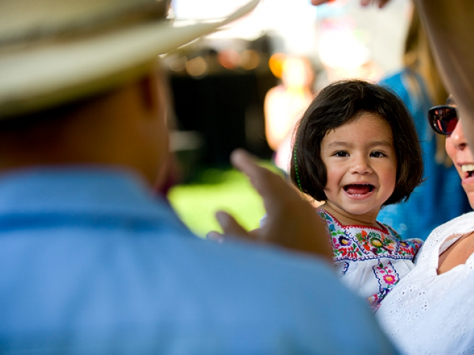 A young girl smiles at someone during the OMCA Dia de los Muertos celebration.