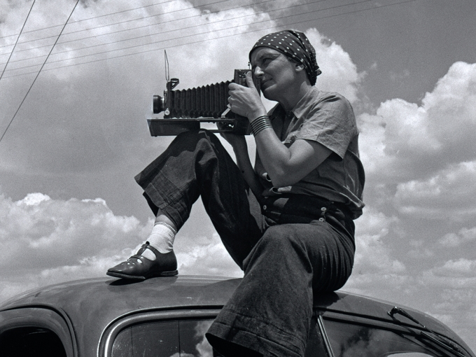 Black and white image of Dorothea Lange holding a large camera while sitting on top of a car