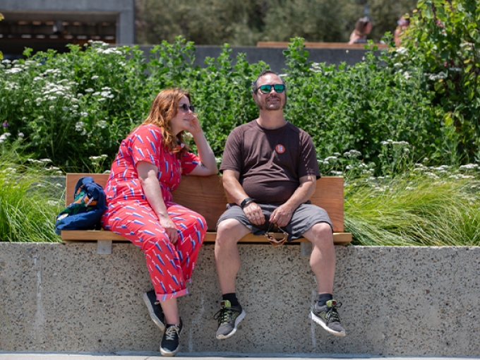 Two people happily converse while sitting on a bench in the OMCA garden.