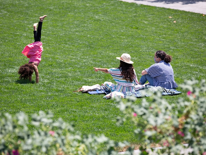 A girl does a cartwheel on the OMCA garden lawn, while her guardian points at her.