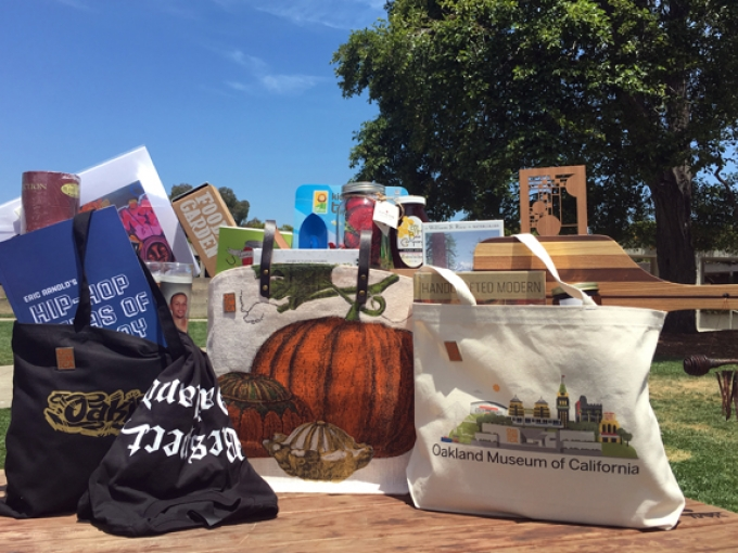 Three tote bags filled with various Oakland Museum of California merchandise sitting on a wooden table in a grassy outdoor setting
