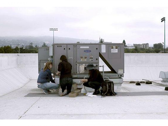 Three people working on an air vent on top of a roof