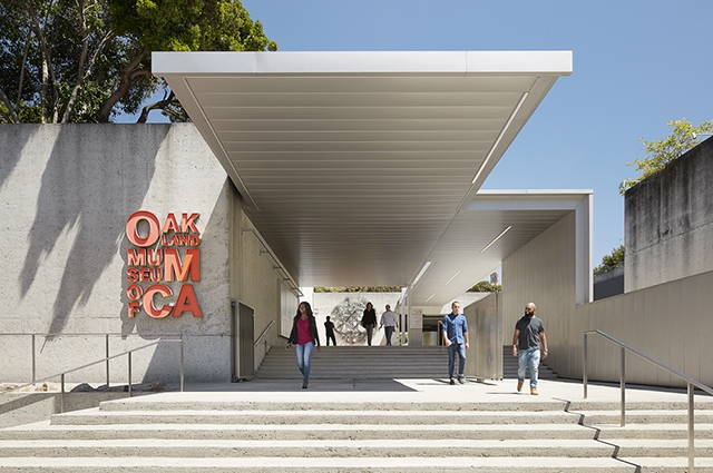 A group of people walking around the Oak Street entrance of OMCA