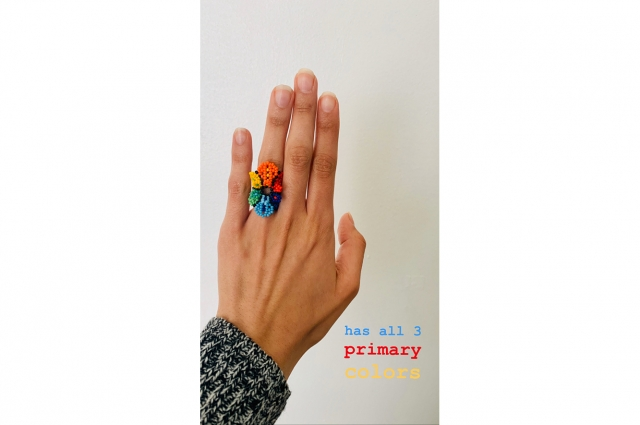 A hand wearing a colorful ring with text that reads: has all 3 primary colors