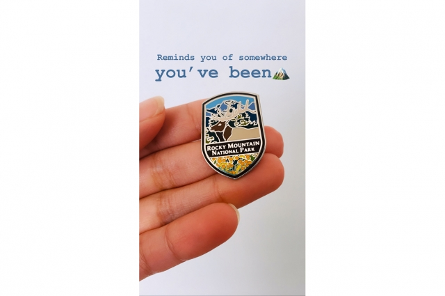 A hand holding a pin from Rocky Mountain National Park with text reading: Reminds you of somewhere you've been