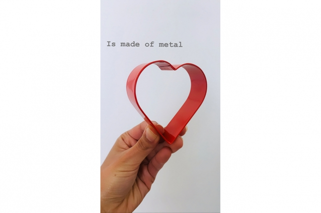A hand holding a heart-shaped cookie cutter with text that reads: Is made of metal