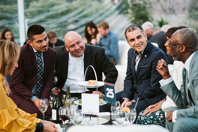 A group of men in fancy suits sit around a table of food and chat