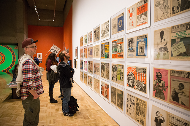 A number of people look at magazine articles on display at the Black Panther exhibit.