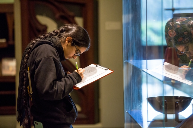 A girl takes notes while standing in front of a display case
