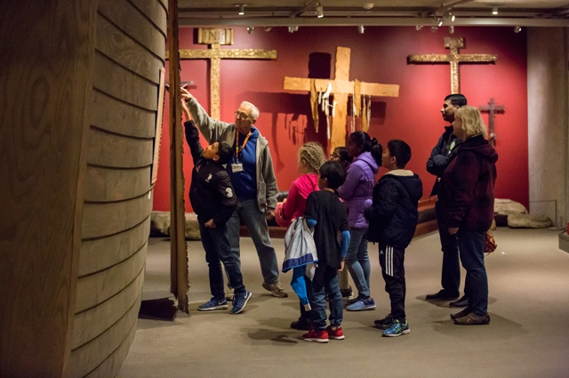 A Docent shows a group of students a large artifact in the Gallery of California History
