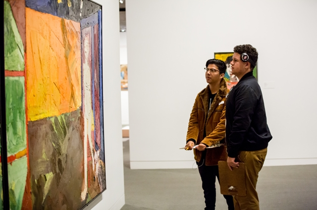 Two boys look at paintings in the Gallery of California Art