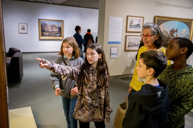 Four students viewing a piece of art in the Gallery of California Art